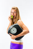 Young woman with scale under her arm and apple Royalty Free Stock Photography