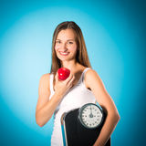 Young woman with scale under her arm and apple Stock Photo
