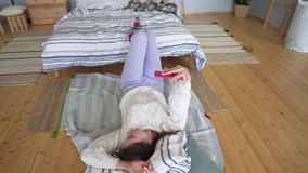 A young woman in a Scandinavian-style apartment is lying on the floor and is photographed on the phone in a red case. 4k stock footage