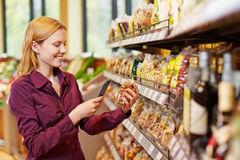 Young woman scanning bag of nuts in supermarket. Young woman scanning barcode of bag of nuts in supermarket with her smartphone Stock Photo
