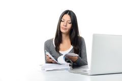 Young Woman Scanning a binder While Using Laptop Royalty Free Stock Photo