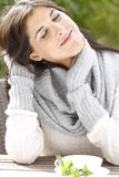 Young woman with scarf and pullover with a cup of tea Royalty Free Stock Photography