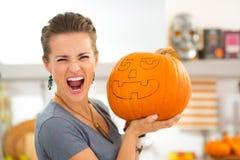 Young woman scaring with big Halloween pumpkin Jack-O-Lantern Stock Image