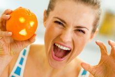 Young woman scaring with orange with hallowing face. Woman scaring with orange with hallowing face Stock Image