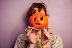 Young woman with scary pumpkin in front of her face Royalty Free Stock Photography
