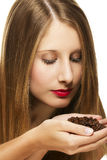 Young woman scenting on a handful of coffee beans Royalty Free Stock Images