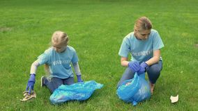 Young woman and schoolgirl giving high five collecting garbage in park, teamwork. Stock footage stock footage