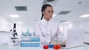 A female scientist writes clinical trial data to a laptop while sitting at a white table in a chemical laboratory. Young woman scientist in white coat and stock video