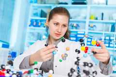 Young woman scientist working at the laboratory. Model of molecule on a Stock Photography