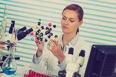 Young woman scientist working at the laboratory. Model of molecule in hand royalty free stock photography
