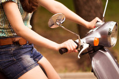 Young woman on scooter in city park. Close up Royalty Free Stock Photography
