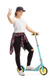 Young woman with a scooter making a peace sign Stock Image