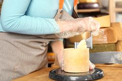 Young woman scraping delicious cheese with girolle. In shop Royalty Free Stock Photo