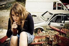 Young woman in the scrapyard. Young woman taking beer in the scrapyard Stock Image