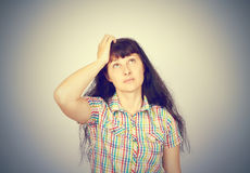 Young woman scratching head, thinking daydreaming deeply about Royalty Free Stock Photography