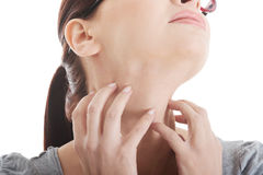 Young woman is scratching her neck. Royalty Free Stock Photos