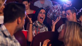 Young woman screaming at cinema. Young women screaming with horror in movie theater, others watching Stock Image