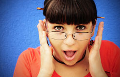 Young woman screaming of joy. Young brunette woman with large brown eyes in glasses holding her head in her hands and screaming with joy Royalty Free Stock Photos