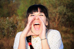 Young woman screaming of joy. Image of a young country girl screaming joyful on a autumn afternoon Stock Photography