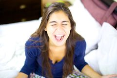Young woman screaming like crazy. Woman at home going mad and depressed Stock Image