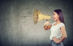 Young woman screaming into loudspeaker. Side view of woman in white t-shirt spreading news and making announcement with loudspeaker stock photography