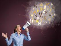 Young woman screaming into a megaphone Stock Photo