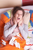 Young woman screaming in pain. Young woman is ill in bed. She is feeling miserable. Ideal medical shot Stock Images