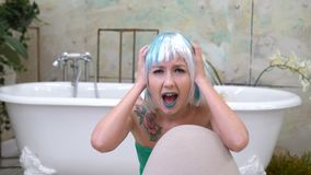 Young woman screaming in terror with hands on her head in bathroom.  stock video footage