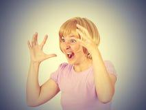 Young woman screams in terror, faces portrait. Stock Photos