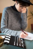 Young woman screenwriter working desktop. Movie clapper on desktop, young pretty woman writing out of focus in background Royalty Free Stock Photo
