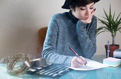 Young woman screenwriter working desktop. Young pretty woman writing on desktop with movie objects, clapper and filmstrip, with cigarette smoke in the air Stock Photo
