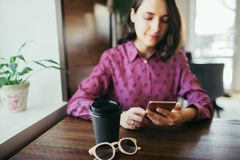 Young woman scrolling her mobile phone, sitting at the table. royalty free stock photography