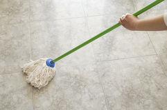 Woman scrubbing floor with a mop Stock Photos