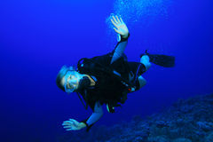 Young Woman Scuba Diver. Swims over a coral reef Stock Images