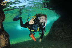 Young woman scuba diving. Young woman scuba diver enters underwater cave stock images