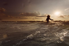 Young woman on sea embracing the the world and the waves Stock Photo