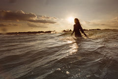 Young woman on sea embracing the the world and the waves Stock Photos