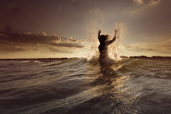 Young woman on sea embracing the the world and the waves Royalty Free Stock Photography