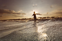 Young woman on sea embracing the the world and the waves Royalty Free Stock Images