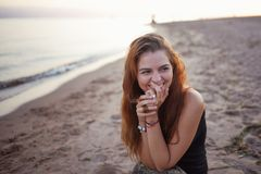 Young woman at sea, good mood and harmony. Beautiful red-haired girl. Cute cheerful young woman portrait at sunset. Young woman at the sea, good mood and harmony Royalty Free Stock Images