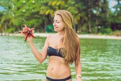 Young woman in the sea with red starfishes stock photography