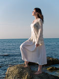 Young Woman on Sea Stone Looking Straight. Young beautiful barefoot woman staying on sea stone looking Royalty Free Stock Image