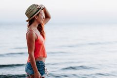 Young woman by the sea at sunset royalty free stock photo