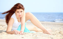 Young woman on seacoast with shell on sand Royalty Free Stock Image