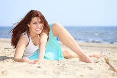 Young woman on seacoast with shell on sand Royalty Free Stock Images