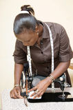 Young woman seamstress. This young woman checks every morning her sewing machine before starting work Stock Photo