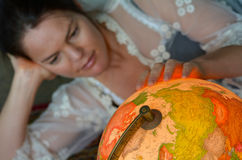 Young woman search for a travel destination on a vintage globe Royalty Free Stock Photo