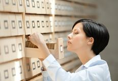 Young woman searches something in card catalog Royalty Free Stock Image