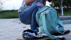 Young woman searching through her backpack stock footage
