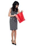 Young woman searching for her gift inside bag Stock Photos
